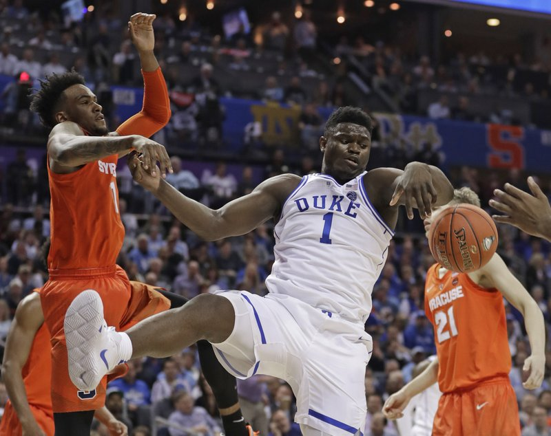 Duke's Zion Williamson, right, battles Syracuse's Oshae Brissett, left, for a rebound during the first half of an NCAA college basketball game in the Atlantic Coast Conference tournament in Charlotte, N. (AP Photo/Nell Redmond)
