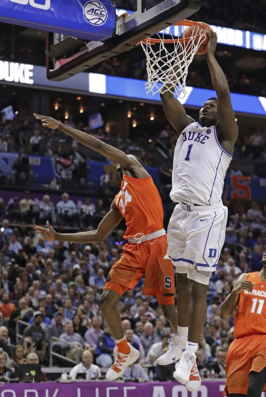 Duke's Zion Williamson (1) dunks past Syracuse's Bourama Sidibe (34) during the first half of an NCAA college basketball game in the Atlantic Coast Conference tournament in Charlotte, N. (AP Photo/Nell Redmond)