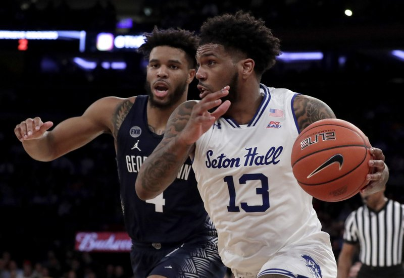 Seton Hall guard Myles Powell (13) drives against Georgetown guard Jagan Mosely (4) during the first half of an NCAA college basketball game in the Big East men's tournament, Thursday, March 14, 2019, in New York. (AP Photo/Julio Cortez)