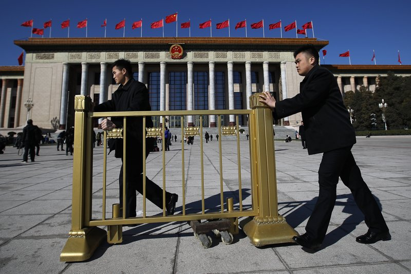 Soldiers in usher uniforms push a barricade as they prepare to close off the Great Hall of the People after the closing session of China's National People's Congress (NPC) in Beijing, Friday, March 15, 2019. (AP Photo/Andy Wong)