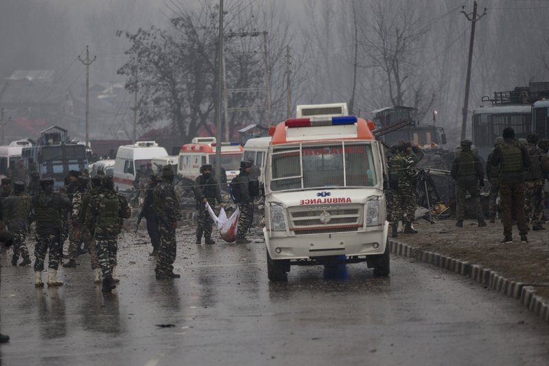 FILE - In this Feb. 14, 2019 file photo, Indian paramilitary soldiers carry the remains of colleagues at the site of a suicide bombing in Pampore, Indian-controlled Kashmir. (AP Photo/Dar Yasin, File)