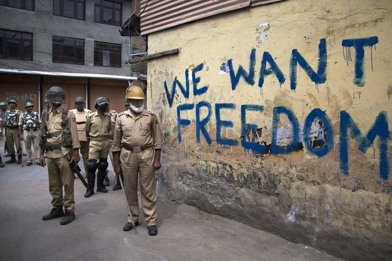 FILE - In this Aug. 12, 2016, file photo, Indian policemen stand guard during a curfew in Srinagar, Indian-controlled Kashmir. (AP Photo/Dar Yasin, File)