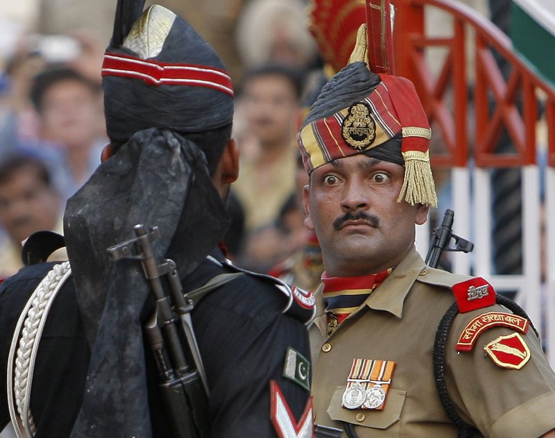 FILE - In this July 19, 2009, file photo, an Indian Border Security Force soldier, right, and a Pakistani Rangers soldier face one another at a daily closing ceremony at the Wagah border post near Lahore, Pakistan. (AP Photo/Vincent Thian, File)