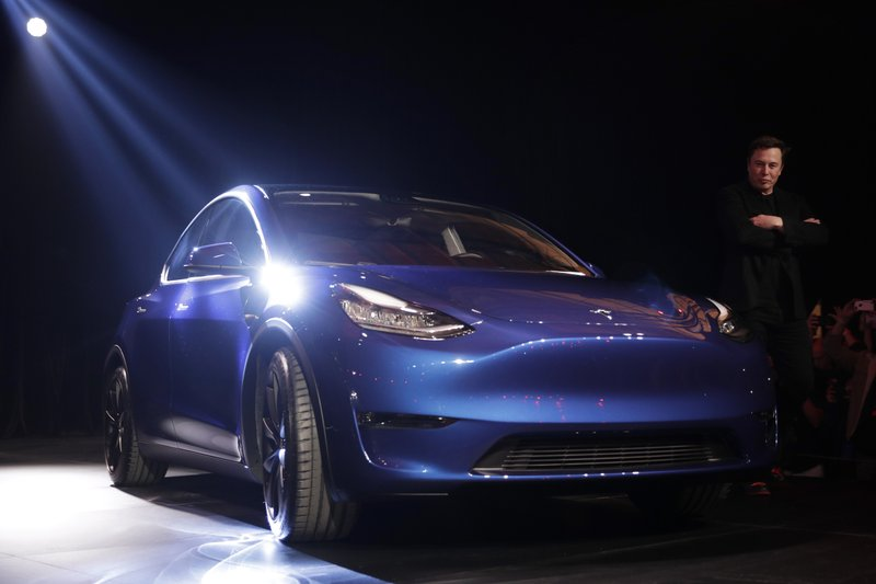 Tesla CEO Elon Musk, right, stands next to the Model Y at Tesla's design studio Thursday, March 14, 2019, in Hawthorne, Calif. (AP Photo/Jae C. Hong)