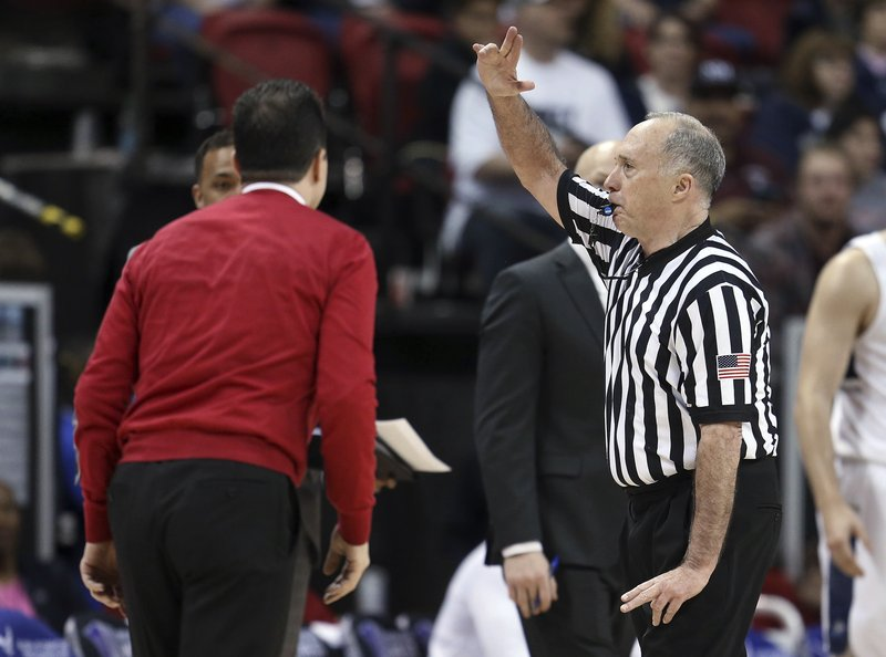 Referee Bob Staffen calls a technical on New Mexico coach Paul Weir, left, dduring the second half of the team's NCAA college basketball game against Utah State in the Mountain West Conference men's tournament Thursday, March 14, 2019, in Las Vegas. (AP Photo/Isaac Brekken)