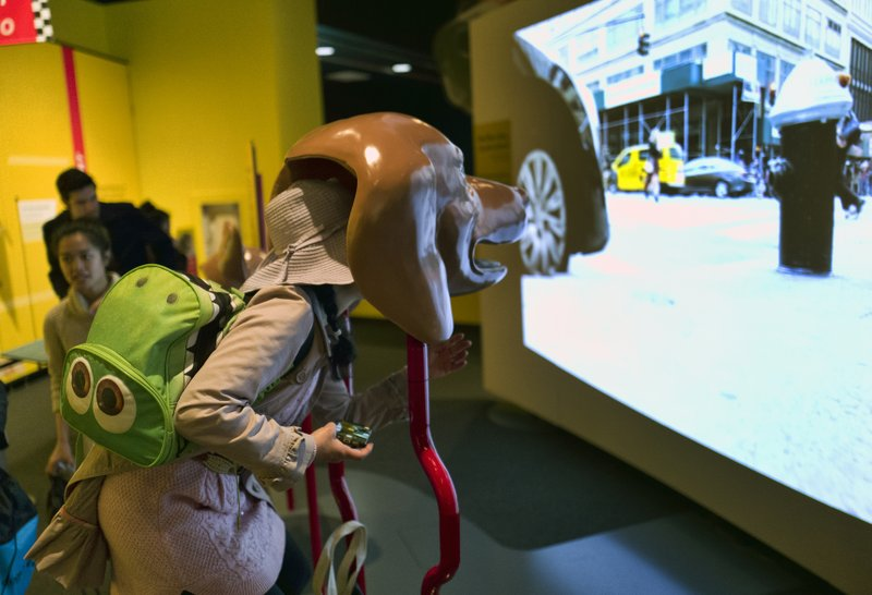 In this Tuesday, March 12, 2019 photo, a visitor takes part in an immersive experience showing visitors how dogs see from inside the head of a dog at the California Science Center in Los Angeles. (AP Photo/Richard Vogel)