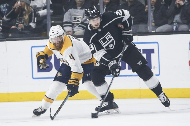 Nashville Predators defenseman Ryan Ellis (4) and Los Angeles Kings forward Dustin Brown (23) vie for the puck during the first period of an NHL hockey game Thursday, March 14, 2019, in Los Angeles. (AP Photo/Ringo H.W. Chiu)