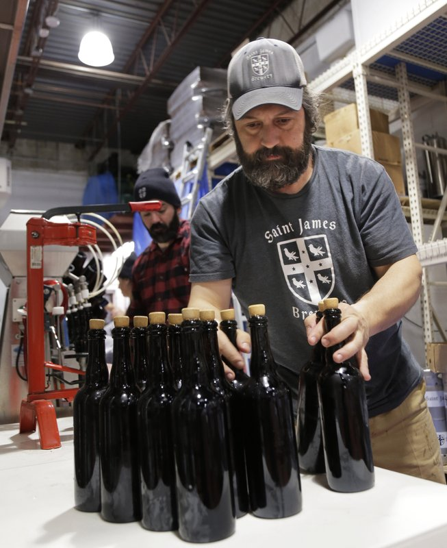 In this March 4, 2019, photo, brewery founder Jamie Adams, right, and John Condzella bottle a batch of their Dubbel beer at the St. (AP Photo/Seth Wenig)