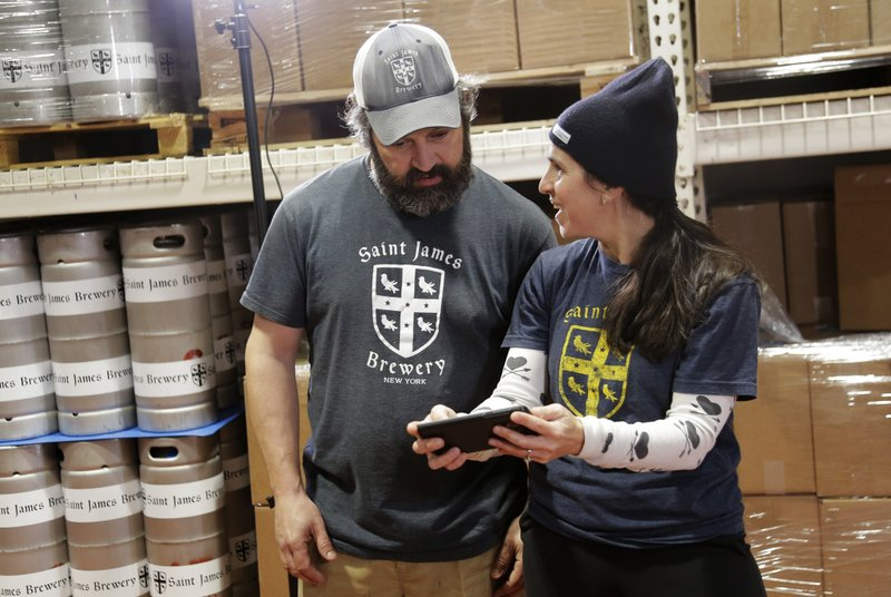 In this March 4, 2019, photo, Jamie Adams and his wife Rachel Adams look at an image of a banner for their new beer, Deep Ascent, at their St. (AP Photo/Seth Wenig)