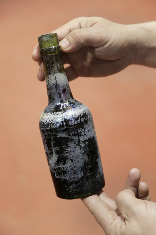 In this March 4, 2019, photo, Jamie Adams displays a bottle of beer recovered from the shipwreck of the SS Oregon at his St. (AP Photo/Seth Wenig)