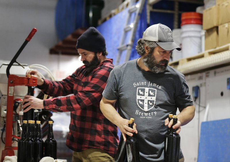 In this March 4, 2019, photo, brewery founder Jamie Adams, right, and John Condzella, left, bottle a batch of their Dubbel beer at the St. (AP Photo/Seth Wenig)