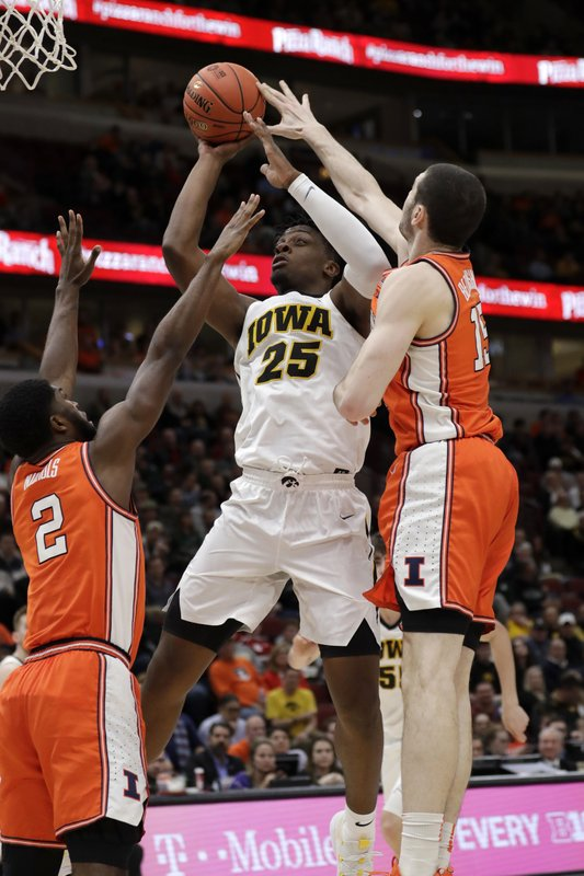 Iowa's Tyler Cook (25) takes a shot against Illinois's Kipper Nichols (2) and Giorgi Bezhanishvili (15) during the second half of an NCAA college basketball game in the second round of the Big Ten Conference tournament, Thursday, March 14, 2019, in Chicago. (AP Photo/Nam Y. Huh)