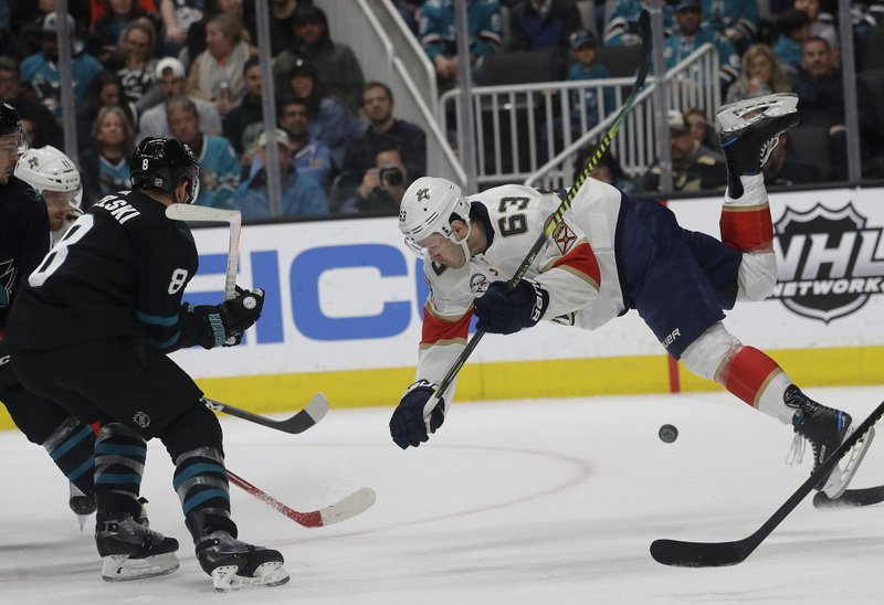 Florida Panthers right wing Evgenii Dadonov (63) falls in front of San Jose Sharks center Joe Pavelski (8) during the second period of an NHL hockey game in San Jose, Calif. (AP Photo/Jeff Chiu)