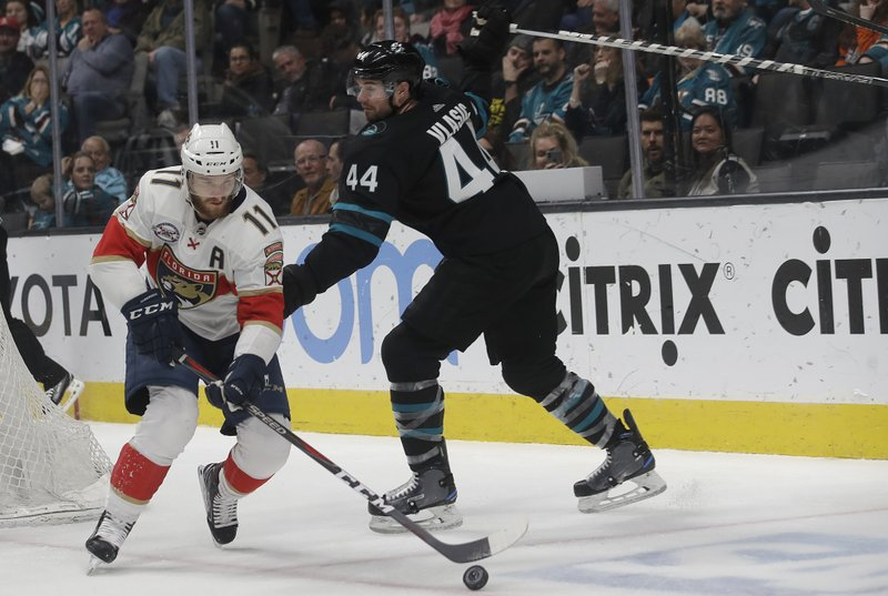 Florida Panthers left wing Jonathan Huberdeau (11) skates with the puck in front of San Jose Sharks defenseman Marc-Edouard Vlasic (44) during the second period of an NHL hockey game in San Jose, Calif. (AP Photo/Jeff Chiu)
