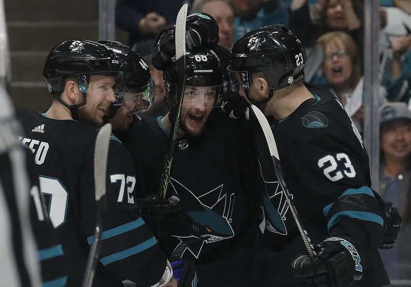 San Jose Sharks center Melker Karlsson, center, is congratulated by teammates after scoring a goal against the Florida Panthers during the first period of an NHL hockey game in San Jose, Calif. (AP Photo/Jeff Chiu)