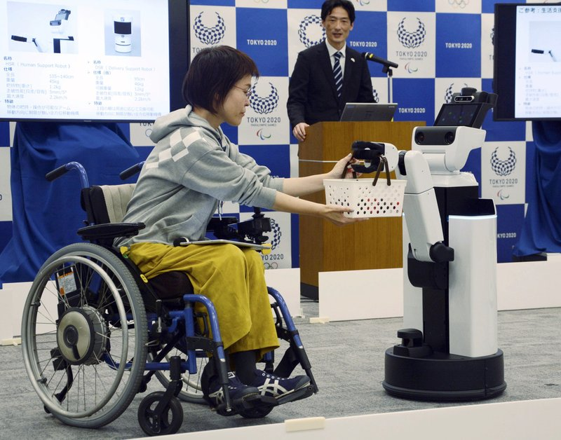 A robot passes a basket containing drinks to a woman in wheelchair during an unveiling event in Tokyo Friday, March 15, 2019. (Kyodo News via AP)