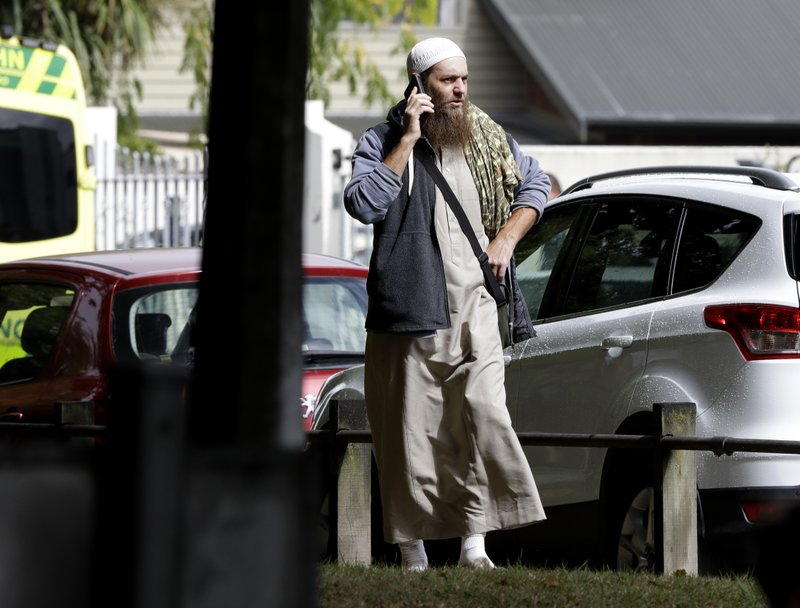 A man talks on his mobile phone across the road from a mosque in central Christchurch, New Zealand, Friday, March 15, 2019. (AP Photo/Mark Baker)