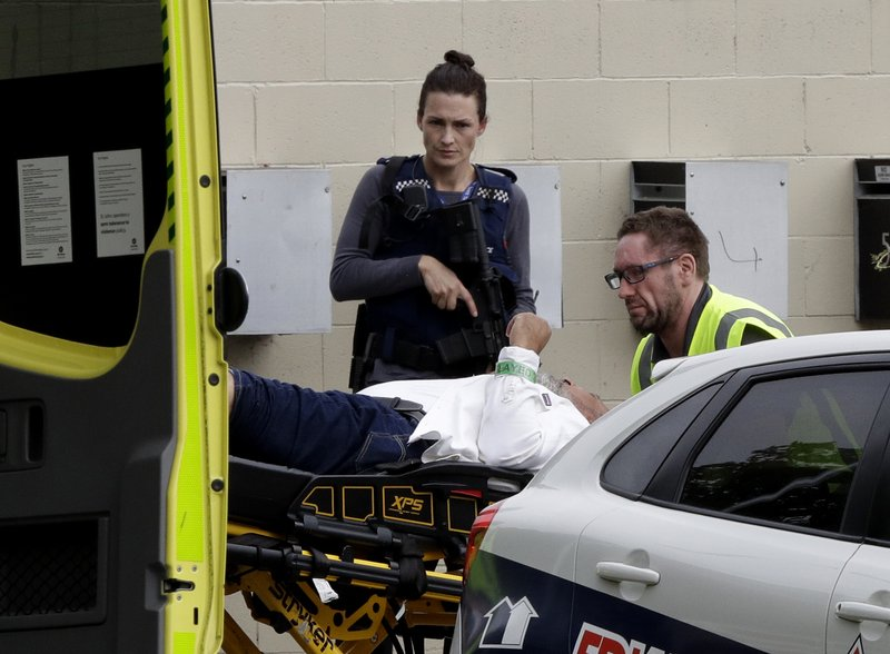 An armed police officer watches as a man is taken by ambulance staff from a mosque in central Christchurch, New Zealand, Friday, March 15, 2019. (AP Photo/Mark Baker)