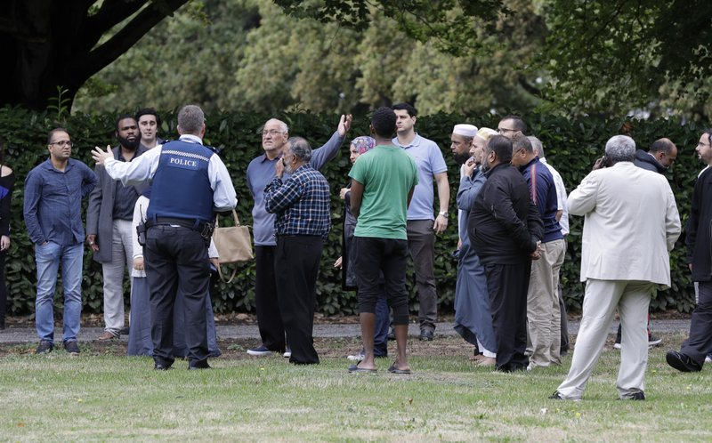 Police talk to witnesses near a mosque in central Christchurch, New Zealand, Friday, March 15, 2019. Multiple people were killed in mass shootings at two mosques full of people attending Friday prayers, as New Zealand police warned people to stay indoors as they tried to determine if more than one gunman was involved. (AP Photo/Mark Baker)