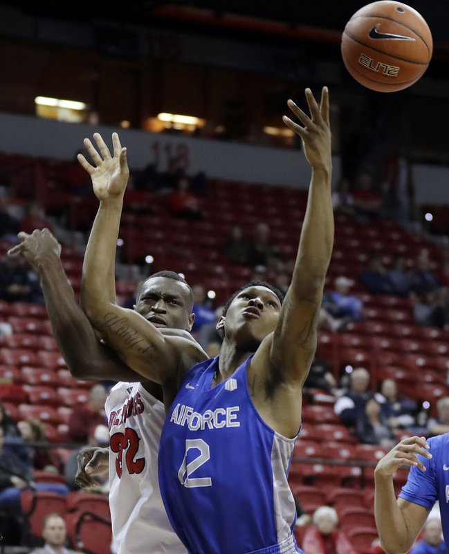 Air Force's Lavelle Scottie (12) and Fresno State's Nate Grimes (32) reach for a rebound during the first half of an NCAA college basketball game in the Mountain West Conference men's tournament Thursday, March 14, 2019, in Las Vegas. (AP Photo/Isaac Brekken)