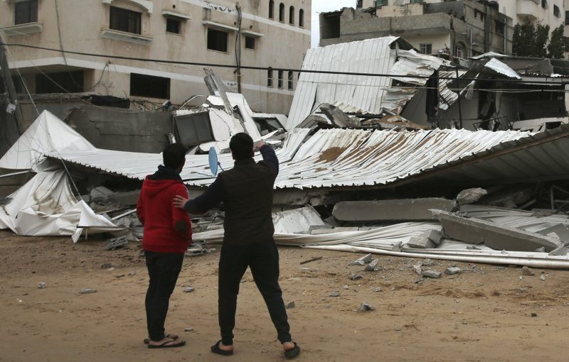 Palestinians inspect the damage of destroyed building belongs to Hamas ministry of prisoners hit by Israeli airstrikes in Gaza City, early Friday, Friday, March 15, 2019. (AP Photo/Adel Hana)