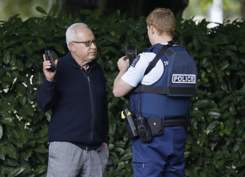A police officer photographs a witness near a mosque in central Christchurch, New Zealand, Friday, March 15, 2019. (AP Photo/Mark Baker)