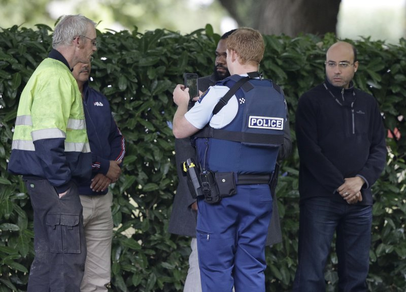 A police officer photographs witnesses near a mosque in central Christchurch, New Zealand, Friday, March 15, 2019. (AP Photo/Mark Baker)