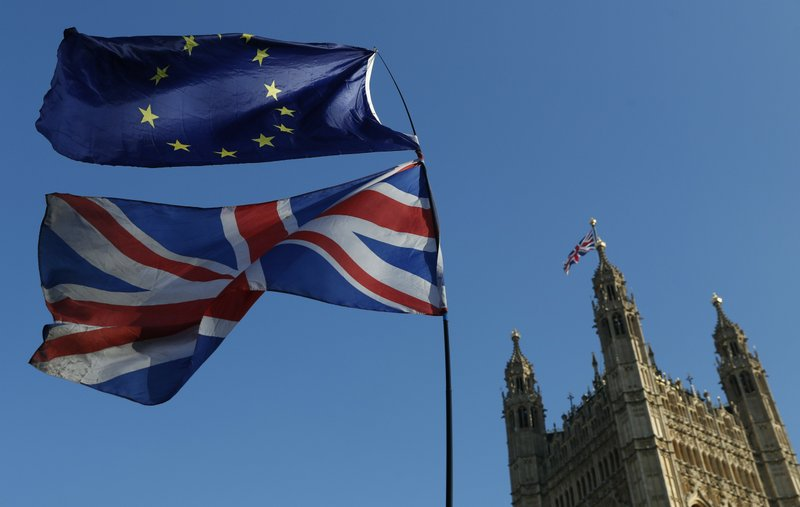 FILE - In this Wednesday, Feb. 27, 2019 file photo the flag of the European Union and the British national flag are flown on poles during a demonstration by remain in the EU outside spporters the Palace of Westminster in London. (AP Photo/Alastair Grant, File)