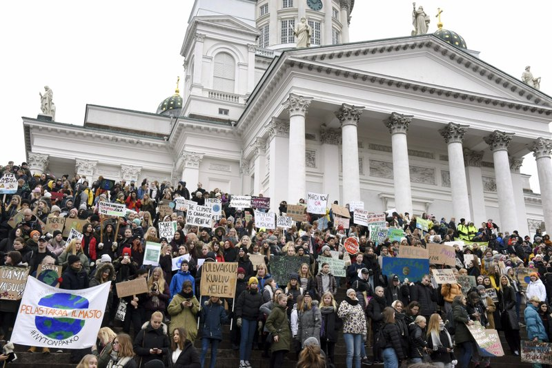 Young demonstrators gather on the steps of the Helsinki Cathedral, prior to the start of a protest march of Finnish youth calling for climate protection,  in Helsinki, Finland, Friday, March 15, 2019. (Heikki Saukkomaa/Lehtikuva via AP)