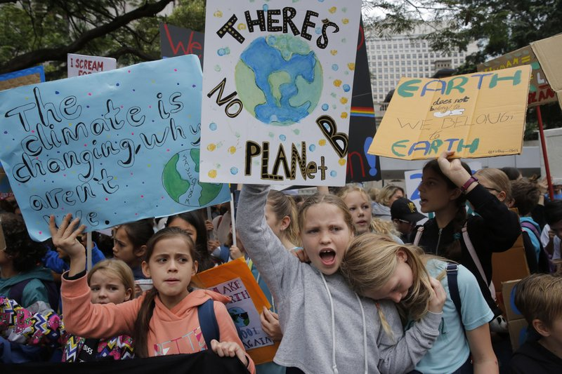 Hundreds of schoolchildren take part in a climate protest in Hong Kong, Friday, March 15, 2019. Students in more than 80 countries and territories worldwide plan to skip class Friday in protest over their governments' failure to act against global warming. (AP Photo/Kin Cheung)