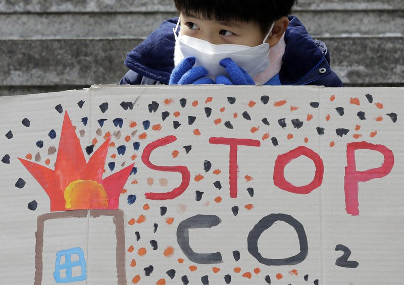 A boy wearing a mask sits behind a banner during a rally for global climate strike for future in Seoul, South Korea, Friday, March 15, 2019. (AP Photo/Lee Jin-man)
