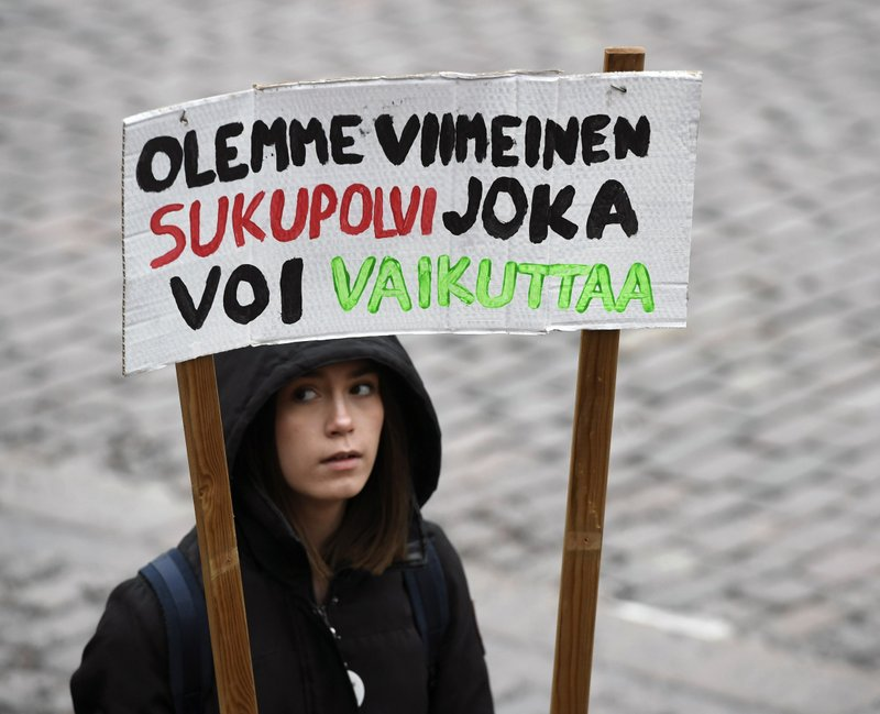 A young demonstrator holds a placard reading 'We are the last generation that can effect', prior to the start of a protest march of Finnish youth calling for climate protection, in Helsinki, Finland, Friday, March 15, 2019. (Heikki Saukkomaa/Lehtikuva via AP)