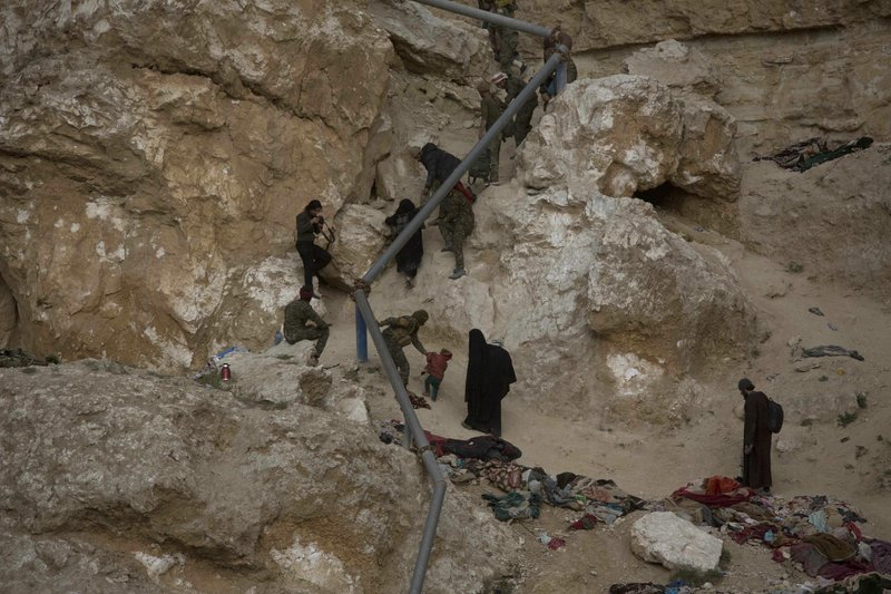 People who left the besieged Islamic State-held village of Baghouz, Syria, scramble up a rocky hillside to be checked by U. (AP Photo/Maya Alleruzzo)