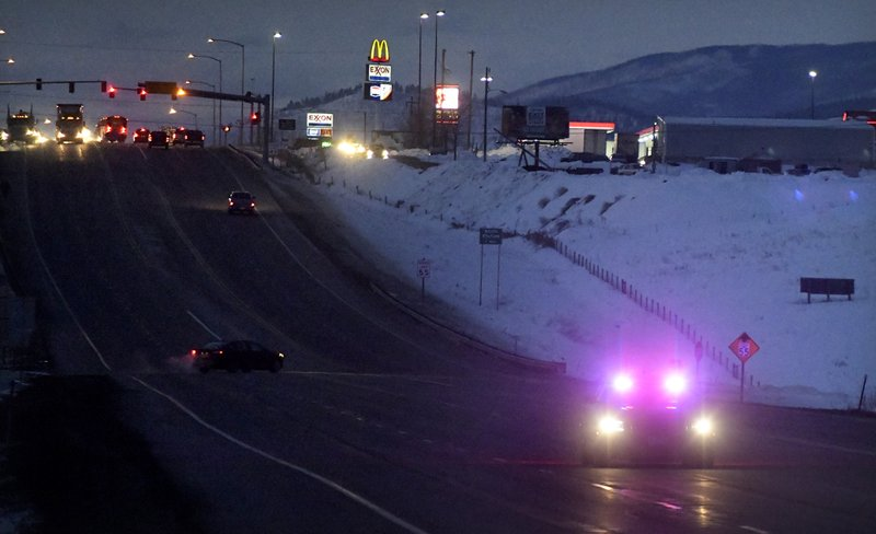 A law enforcement officer drives down Highway 93 during the manhunt for a suspect in a Montana Highway Patrol officer's shooting on Friday, March 15, 2019, in Missoula, Mont. (Tommy Martino/The Missoulian via AP)