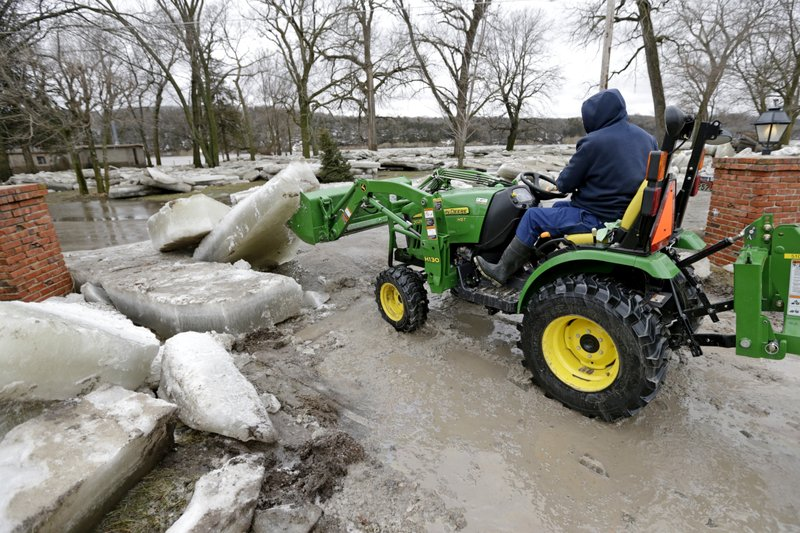 Chad Freeman works to clear thick ice slabs from his property in Fremont, Neb., Thursday, March 14, 2019, after the ice-covered Platte River flooded it's banks. (AP Photo/Nati Harnik)