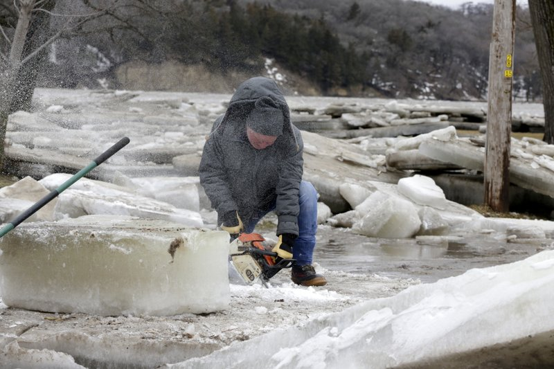 Jim Freeman tries to saw through thick ice slabs on his property in Fremont, Neb., Thursday, March 14, 2019, after the ice-covered Platte River flooded it's banks. (AP Photo/Nati Harnik)