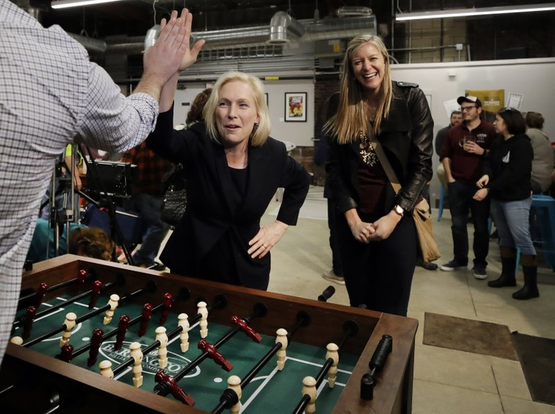 Democratic presidential candidate Sen. Kirsten Gillibrand, D-N.Y., high-fives a foosball opponent as partner Casey Leach of Manchester, N. (AP Photo/Elise Amendola)