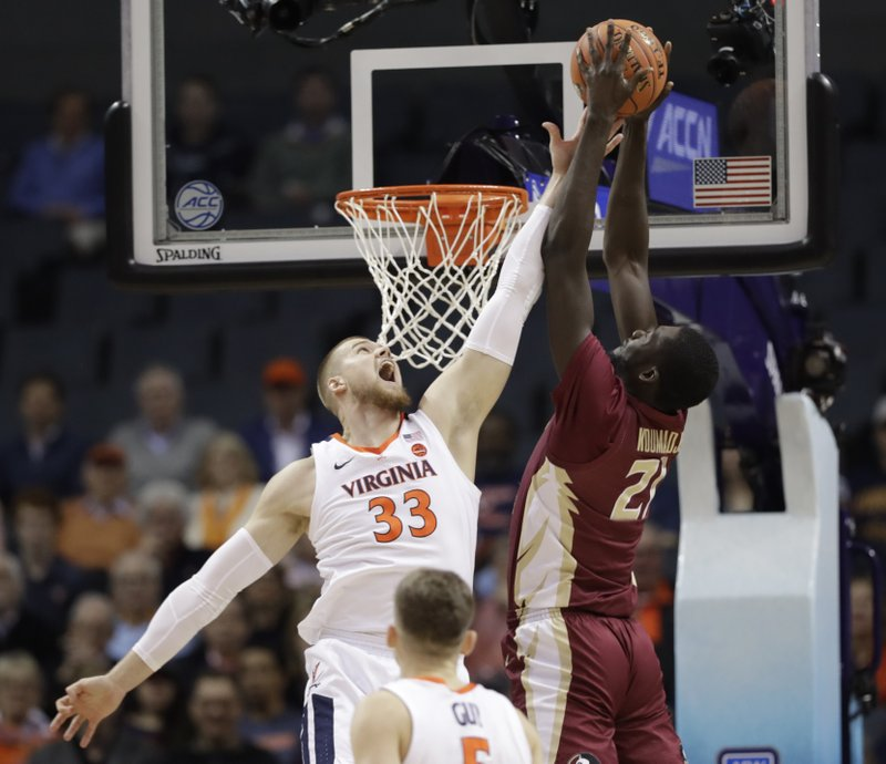 Florida State's Christ Koumadje (21) tries to dunk against Virginia's Jack Salt (33) during the first half of an NCAA college basketball game in the Atlantic Coast Conference tournament in Charlotte, N. (AP Photo/Chuck Burton)