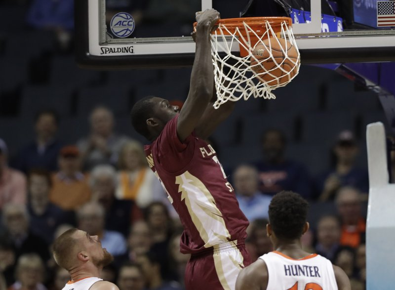 Florida State's Christ Koumadje (21) dunks against Virginia during the first half of an NCAA college basketball game in the Atlantic Coast Conference tournament in Charlotte, N. (AP Photo/Chuck Burton)