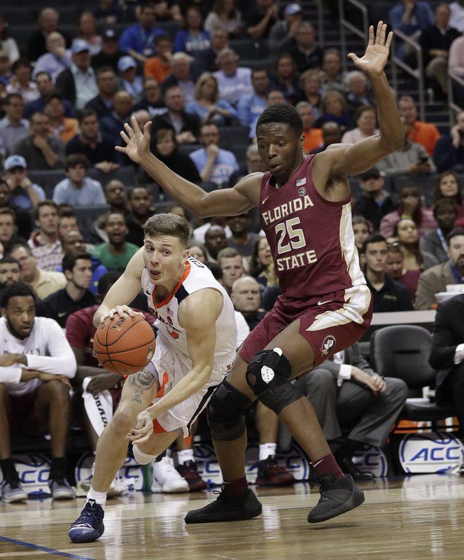 Virginia's Kyle Guy, left, drives past Florida State's Mfiondu Kabengele (25) during the first half of an NCAA college basketball game in the Atlantic Coast Conference tournament in Charlotte, N. (AP Photo/Chuck Burton)
