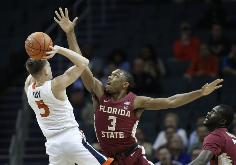 Virginia's Kyle Guy (5) tries to shoot over Florida State's Trent Forrest (3) during the first half of an NCAA college basketball game in the Atlantic Coast Conference tournament in Charlotte, N. (AP Photo/Nell Redmond)