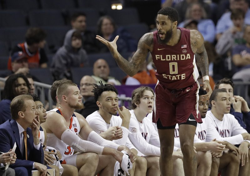 Florida State's Phil Cofer (0) gestures toward the Virginia bench after making a basket during the first half of an NCAA college basketball game in the Atlantic Coast Conference tournament in Charlotte, N. (AP Photo/Chuck Burton)
