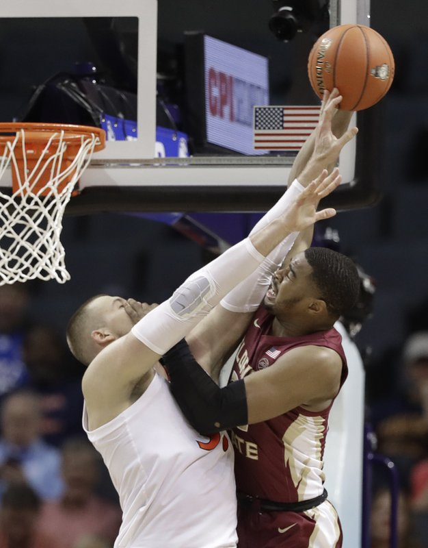Florida State's Christ Koumadje, right, is fouled by Virginia's Jack Salt, left, during the first half of an NCAA college basketball game in the Atlantic Coast Conference tournament in Charlotte, N. (AP Photo/Chuck Burton)