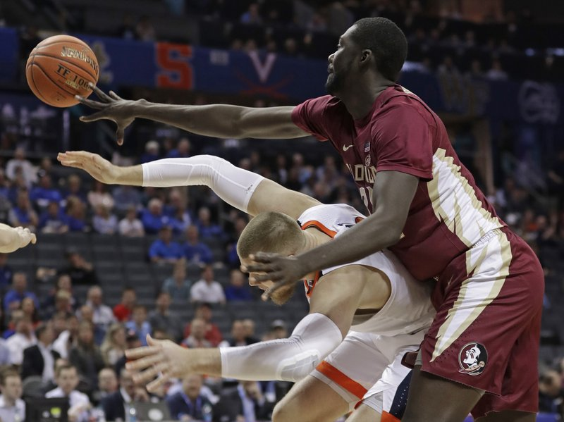 Florida State's Christ Koumadje, top, knocks the ball from Virginia's Jack Salt, bottom, during the first half of an NCAA college basketball game in the Atlantic Coast Conference tournament in Charlotte, N. (AP Photo/Nell Redmond)