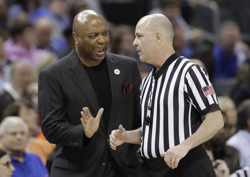 Florida State head coach Leonard Hamilton, left, argues a call during the first half of an NCAA college basketball game against Virginia in the Atlantic Coast Conference tournament in Charlotte, N. (AP Photo/Chuck Burton)