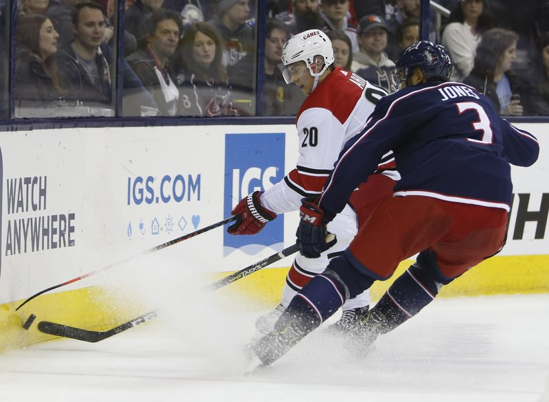 Carolina Hurricanes' Sebastian Aho, left, of Finland, and Columbus Blue Jackets' Seth Jones fight for a loose puck during the first period of an NHL hockey game Friday, March 15, 2019, in Columbus, Ohio. (AP Photo/Jay LaPrete)