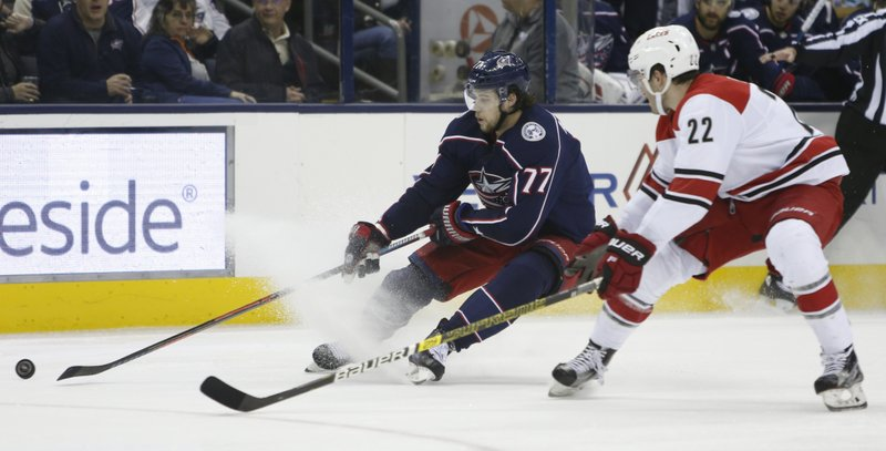 Columbus Blue Jackets' Josh Anderson, left, tries to control the puck up as Carolina Hurricanes' Brett Pesce defends and during the first period of an NHL hockey game Friday, March 15, 2019, in Columbus, Ohio. (AP Photo/Jay LaPrete)