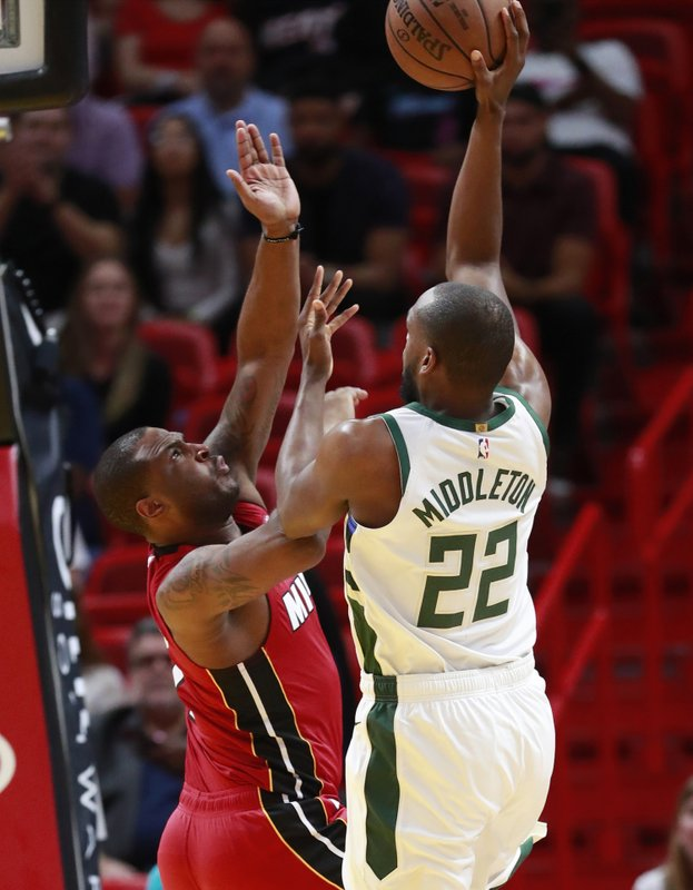 Milwaukee Bucks forward Khris Middleton (22) shoots against Miami Heat guard Dion Waiters during the first half of an NBA basketball game Friday, March 15, 2019, in Miami. (AP Photo/Wilfredo Lee)