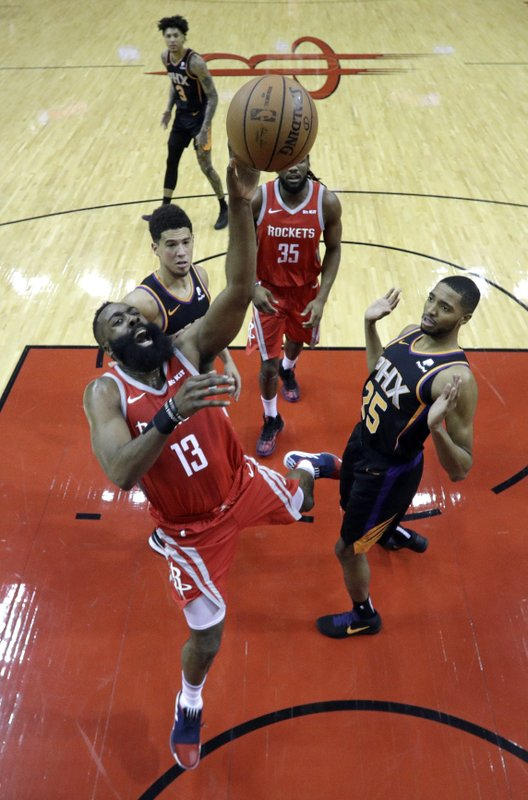 Houston Rockets' James Harden (13) shoots as Phoenix Suns' Mikal Bridges (25) and Devin Booker, left, defend during the first half of an NBA basketball game Friday, March 15, 2019, in Houston. (AP Photo/David J. Phillip)