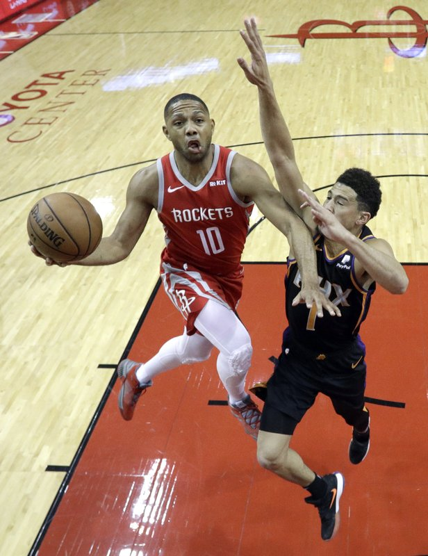 Houston Rockets' Eric Gordon (10) goes up for a shot as Phoenix Suns' Devin Booker (1) defends during the first half of an NBA basketball game Friday, March 15, 2019, in Houston. (AP Photo/David J. Phillip)